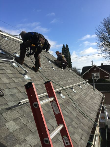 COURTESY ABUNDANT SOLAR - An Abundant Solar installer attaches a solar panel to a residential roof. Such projects could cost Oregon homeowners nearly twice as much next year with the loss of a state tax credit.