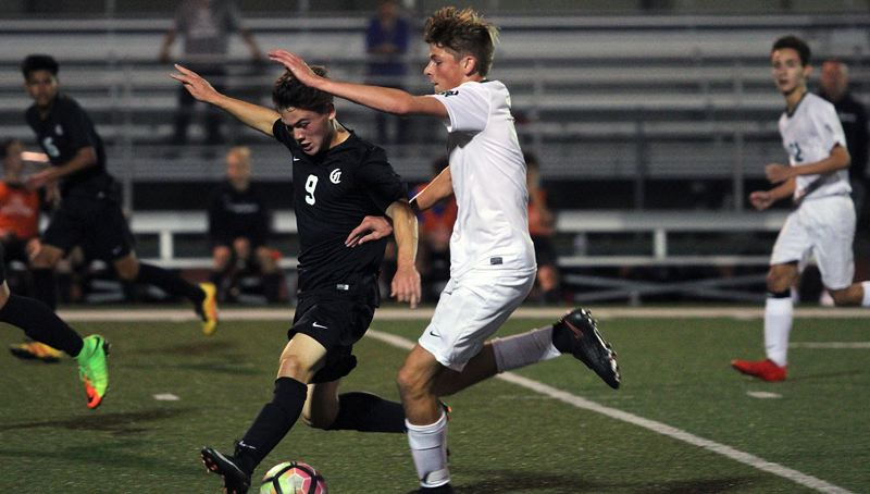 TIDINGS PHOTO: MILES VANCE - West Linn's Ben Walker (right) and Clackamas' Keanu Cano race for possession of the ball during the two teams' 0-0 tie at West Linn High School on Thursday.