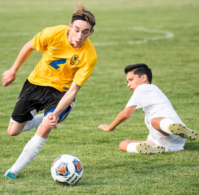 LON AUSTIN/CENTRAL OREGONIAN - Thomas Milat controls the ball as he goes around an attempted slide tackle from Marques Montanez, of Ridgeview. The Ravens scored eight consecutive goals to erase a one-goal Crook County lead and take an 8-1 victory in the non-league matchup.