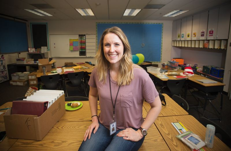 OUTLOOK PHOTO: JOSH KULLA - Amanda Ewing, a new fifth-grade teacher at Kelly Creek Elmentary School in the Gresham-Barlow School District, readies her classroom for her first year of teaching.