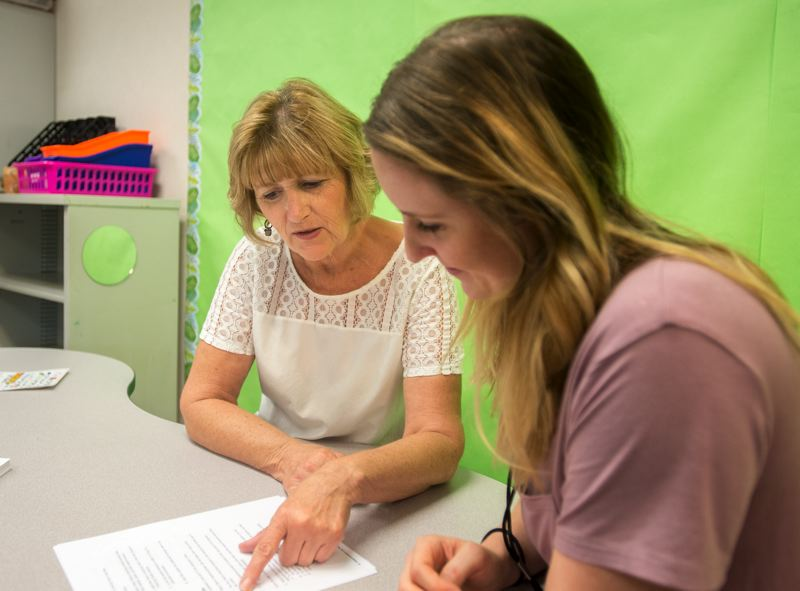 OUTLOOK PHOTO: JOSH KULLA - Nancy Torbert, principal of Kelly Creek, goes over the finer points of student testing with Amanda Ewing, a new fifth-grade teacher.
