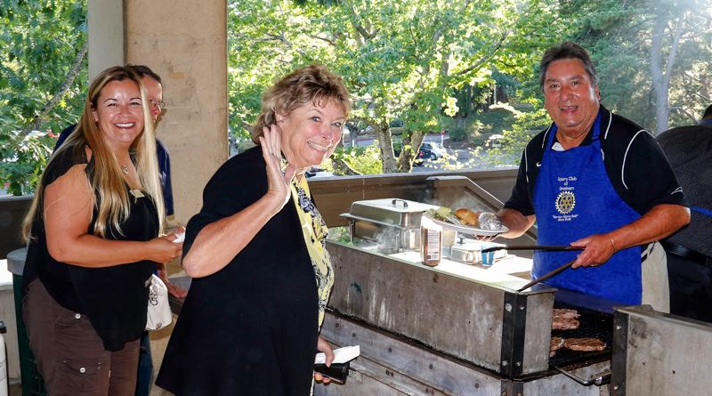 COURTESY PHOTO - Gresham Chamber CEO Lynn Snodgrass awaits her steak, fresh off the grill and cooked to perfection by Rotarian Bob Avila during the 2016 Gresham Rotary Steak Fry at Mt. Hood Community College. At far left is MHCC board member Tamie Tlustos Arnold.