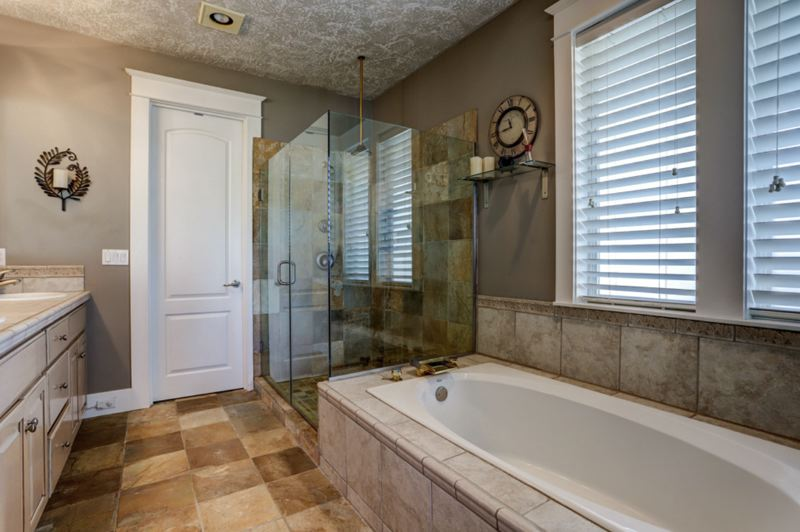 PHOTO COURTESY MICHAEL PATRICK - A walk-in glass-walled shower, full-length tub and walk-in closet are all provided in the master bathroom.