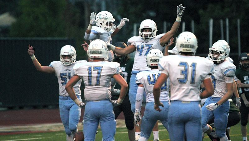 REVIEW PHOTO: MILES VANCE - Lakeridge's Joe Marini (No. 47) celebrates with teammates after recovering a Wilson fumble at the Trojans' 1-yard line during his team's 55-0 win at Wilson High School on Friday.