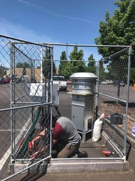 COURTESY JESSICA APPLEGATE  - A DEQ technician dismantles an air quality monitor installed in a parking lot near Bullseye Glass. The agency determined the company's toxic emission problem was resolved by a $1 million-plus improvement project.