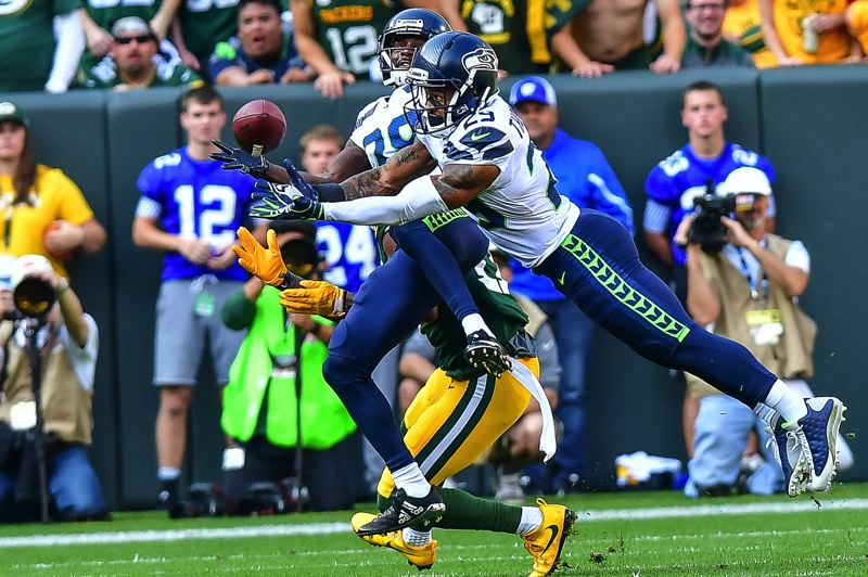 PHOTO BY MICHAEL WORKMAN - Seattle's Richard Sherman breaks up a Green Bay pass attempt.