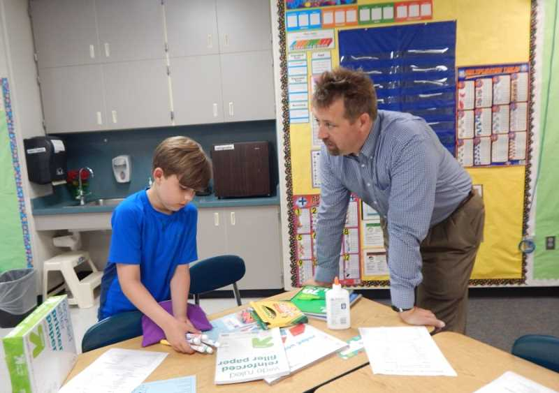 REGAL COURIER PHOTO: BARBARA SHERMAN - Tobias Schaefer puts away his school supplies under the watchful eye of his dad Seth in Brenda Croskrey's third-grade classrroom at Deer Creek Elementary; luckily, third-grade students were not affected by the delayed delivery of a portable.