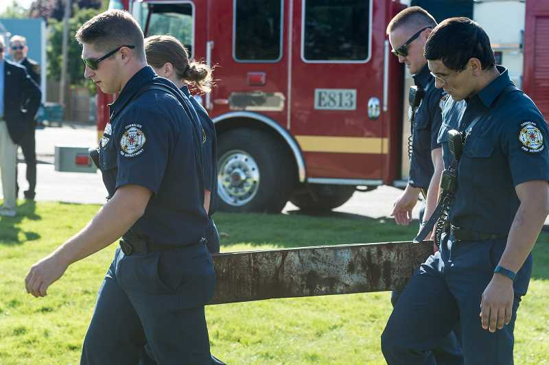 NEWS-TIMES PHOTO: CHRISTOPHER OERTELL - Firefighters carry a portion of a steel support beam from the wreckage of the World Trade Center to a place of honor during a 9/11 memorial ceremony Monday in Forest Grove, which drew about 50 people.