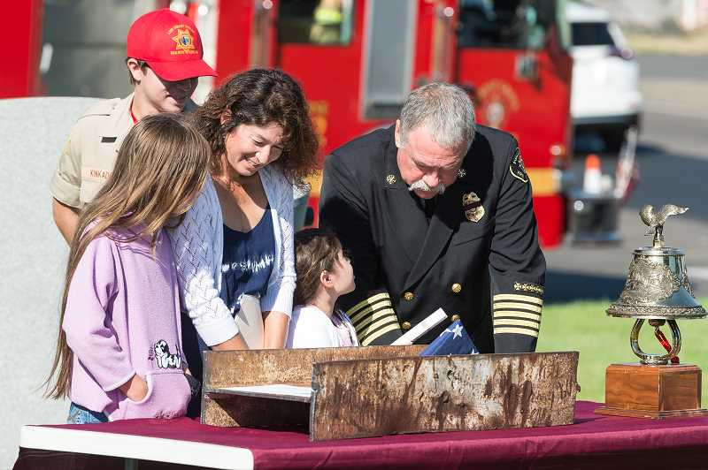 NEWS-TIMES PHOTO: CHRISTOPHER OERTELL - Forest Grove Fire Chief Michael Kinkade gathers with his family to inspect the relic from the 9/11 attacks in New York.