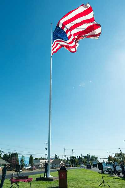 NEWS-TIMES PHOTO: CHRISTOPHER OERTELL - A firefighter lowers the flag to half mast during the ceremony.