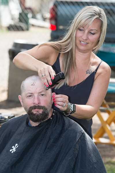 NEWS-TIMES PHOTO: CHRISTOPHER OERTELL - Beatrice Boden shaves the head of Shawn Thomson during the St. Baldrick's Foundation event at Sunset Grove Golf Club last Saturday, Sept. 9.