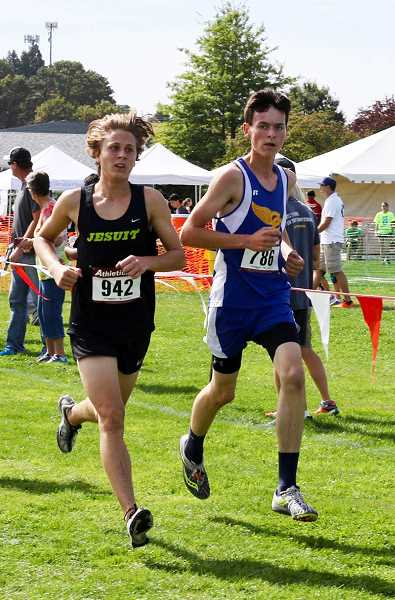 PHOTO COURTESY OF RACHEL WENTE-CHANEY - Cade Catterson runs alongside a Jesuit runner during the Ash Creek XC Festival in Monmouth. Catterson, a sophomore, ran the fastest time of his career at the race.