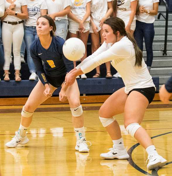 LON AUSTIN/CENTRAL OREGONIAN - Mekynzie Wells passes a ball during the Cowgirls' loss to Bend as Kennedy Buckner backs her up. Wells finished the match with 21 digs.