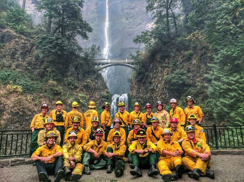 COURTESY PHOTO - A combined group of Portland-metro area firefighters protected the Multnomah Falls Lodge from the Eagle Creek Fire last week, including Gaston firefighter Micah Poling (second from left in front row) and Forest Grove firefighter Jeff Bade (third from right in front row). Not pictured are Gaston's Randy Hoodenpyl and Mark Johnston, who were on duty with their agency's water tender when the photo in front of Multnomah Falls was shot.