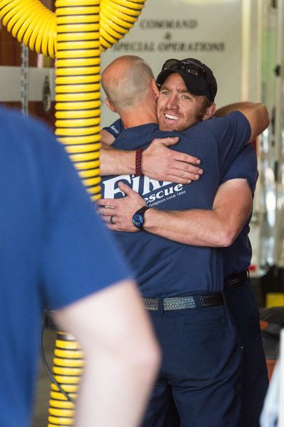 NEWS-TMES PHOTO: CHRISTOPHER OERTELL - Forest Grove Fire & Rescue firefighter Geoff McFarland gets a welcoming hug after returning from working nearly a week at the Eagle Creek Fire in the Columbia River Gorge.