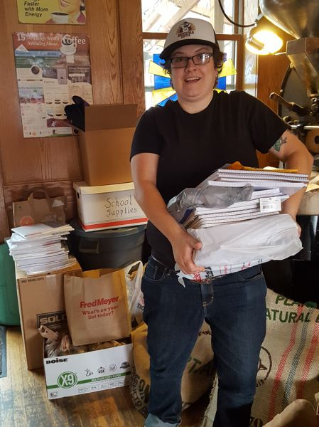 PHOTO COURTESY: LESLIE ROBINETTE - Lisa Halcom, owner of Happyrock Coffee Roasters, helps pack up donated school supplies.