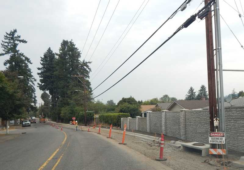 BARBARA SHERMAN - Work continued on Fischer Road on Sept 7 as a flagger controlled traffic, limiting travel to one direction at a time just west of Queen Anne. The last three 6-foot-high concrete fence panels on the right will be replaced with 8-foot-high panels to match the other ones.