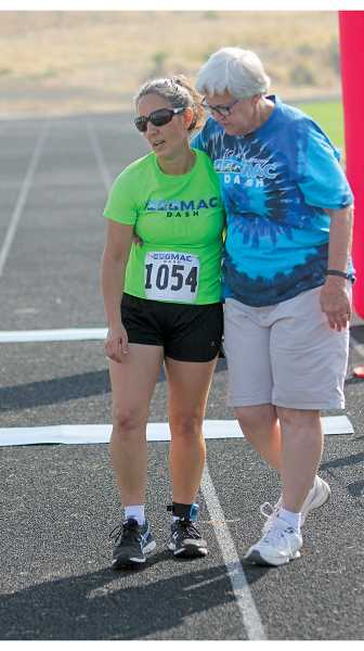 "WILL DENNER/MADRAS PIONEER - Former MAC Dash race director Suzy El-Attar (left), who competed in the coed division on the team, ""Doug, Dave and the Diva"" is greeted by Margee O'Brien at the finish line."