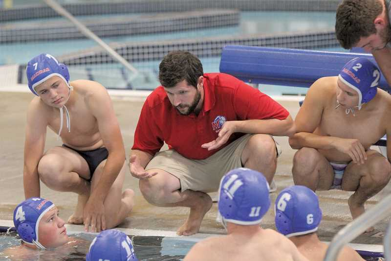 WILL DENNER/MADRAS PIONEER - Madras head coach Matt Hauge (center) talks to his team during their season-opener last Wednesday, a 14-7 loss to Bend at home.