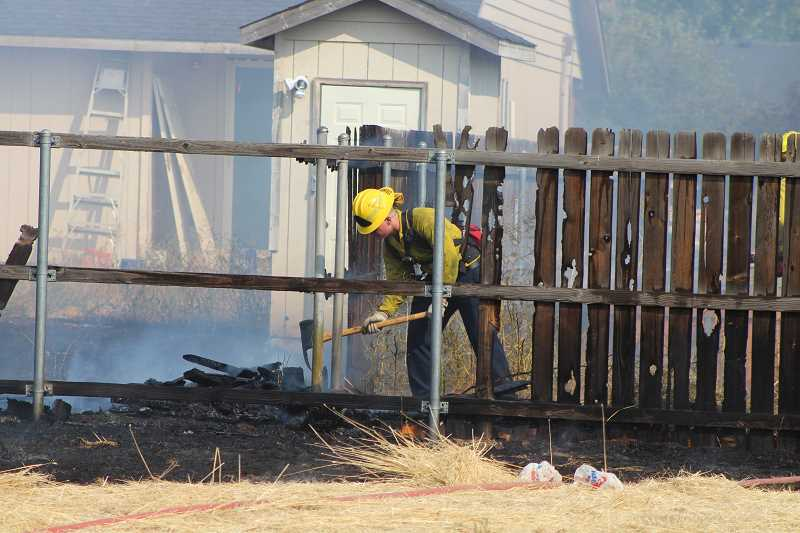 HOLLY SCHOLZ/CENTRAL OREGONIAN - A firefighter works to put out the fire that erupted Thursday afternoon off of Peters Road, damaging two sheds and fences.