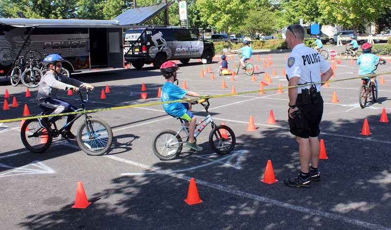 THE TIMES: MANDY FEDER-SAWYER - Beaverton Police Officer Doc Coulson watches as people of all ages cruise the bicycle course during Bike Beaverton on Sunday, Sept. 10.
