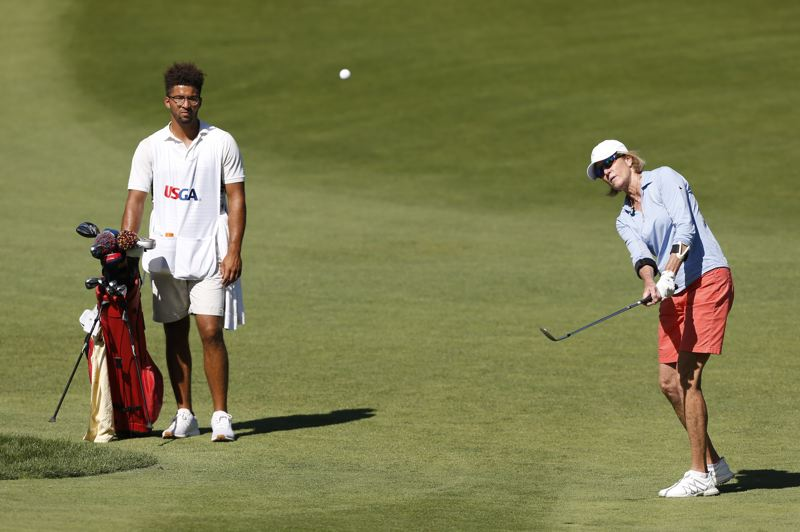 COPYRIGHT USGA/STEVEN GIBBONS - Lisa McGill (right) of Philadelphia, flanked by local caddy Jonah Pemberton, pitches to a green at Waverley Country Club on Tuesday during the U.S. Senior Women's Amateur.