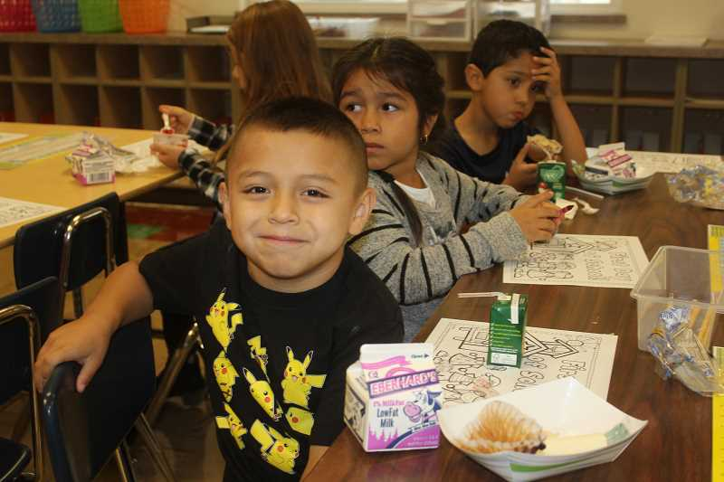 SUSAN MATHENY/MADRAS PIONEER - First-graders Enrique Avila, left, Faviola Anguiano and Roman Barrera start out their first day of school with breakfast in Hayley Proctor's room at Buff Elementary, on Sept. 6.