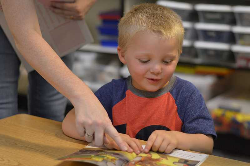 SPOKESMAN PHOTO: CLARA HOWELL  - Asher Smith, 5, and his kindergarten teacher Traci Hallock-Gross, look at a picture Asher finds fascinating during morning reading time.