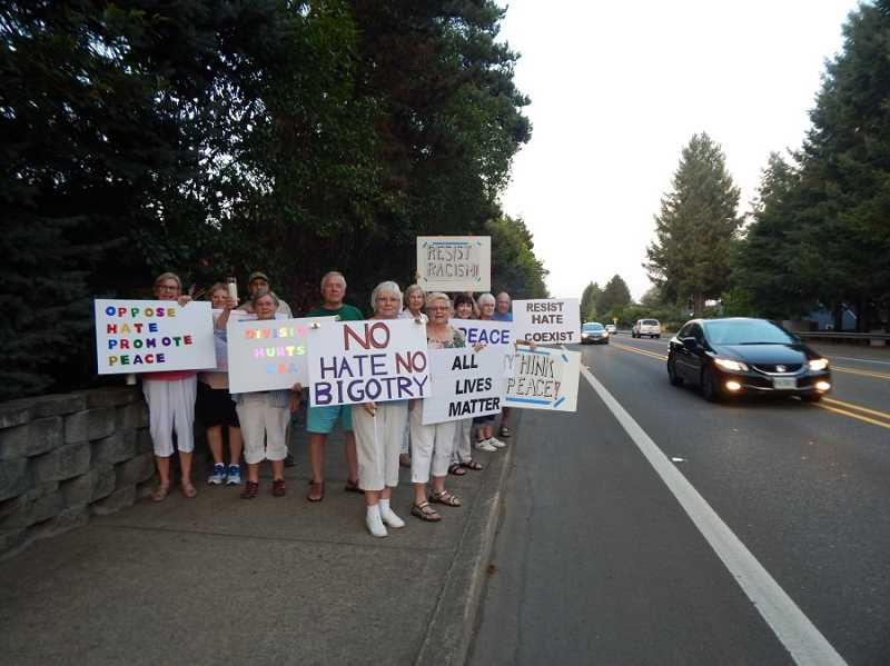 BARBARA SHERMAN - At dusk on Aug. 29 along the north side of Durham Road, Summerfield residents promote peace and denounce hate to inspire drivers passing by during just one of many events in response to the violent rally in Charlottesville, Va., on Aug. 12.