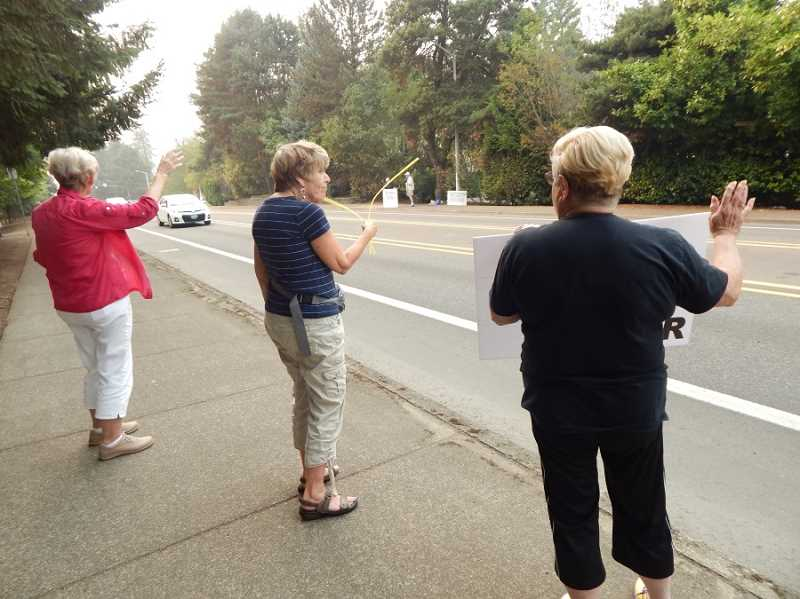 BARBARA SHERMAN - Standing on the south side of Durham Road, (from left) Barbara Roth, Michele Seligmam and Karen Zwerling wave at drivers while more members of their group draw attention with their peace signs on the other side of the street.