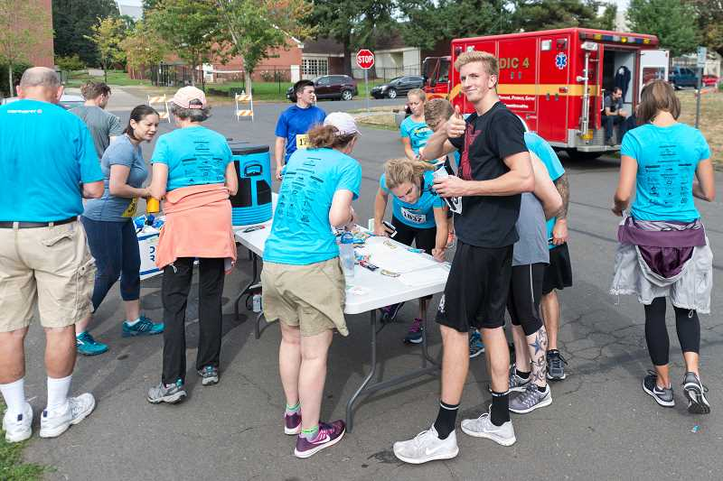 NEWS-TIMES PHOTO: CHRISTOPHER OERTELL - Runners look at their race results after the Forest Grove Lions 17th Annual Run & Walk for Sight.