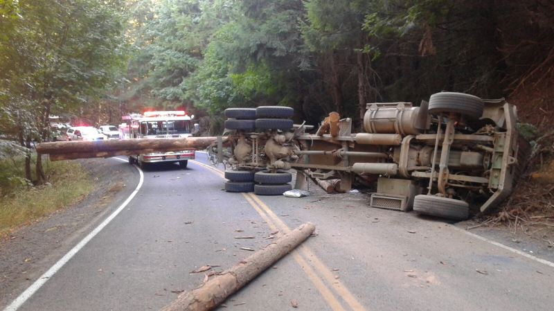 COLUMBIA COUNTY SHERIFF'S OFFICE PHOTO - A fire engine arrives at the scene of an overturned truck hauling logs on Scappoose-Vernonia Highway. The crash shut down the road for roughly four hours Monday afternoon and the truck's driver was airlifted to a nearby hospital.
