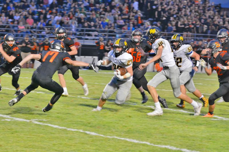 SPOTLIGHT PHOTO: JAKE MCNEAL - Lions senior running back Cody Leanna (27), with help from sophomore tight end Tanner McTeigue (14) and sophomore lineman Alden Finch (52), eludes Scappoose tacklers.