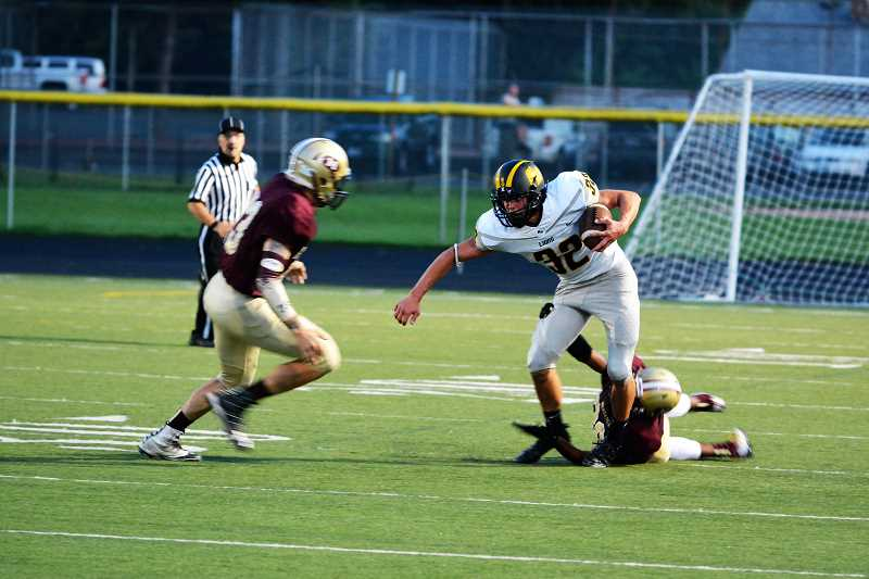 SPOTLIGHT PHOTO: JAKE MCNEAL - Lions senior tight end Zane Weis (32) breaks a Milwaukie tackle and engages another.