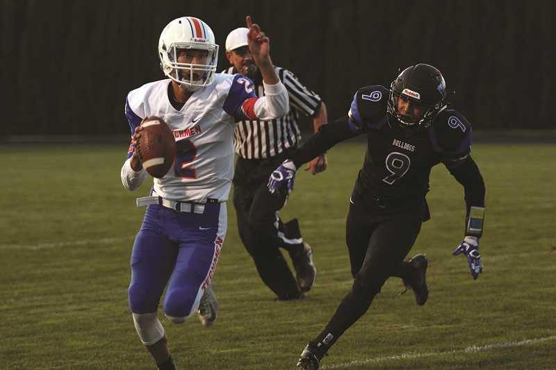 PHIL HAWKINS - Benson quarterback Tyler Phillips scrambles loose with Woodburn's Jonathan Serrano close on his heels in the Bulldogs' 24-13 victory over the Techmen on Friday.