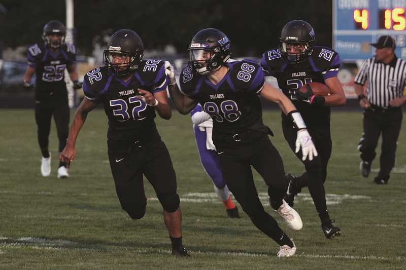 PHIL HAWKINS - Woodburn's Juan Sanchez and Chandler Vargas pave the wave for punt returner Marcos Orta in the Bulldogs' 24-13 victory over Benson on Friday.