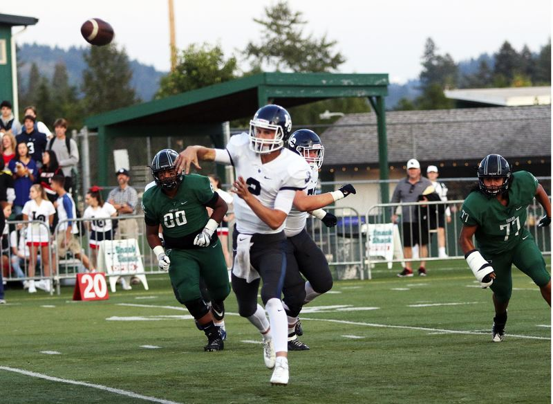DAN BROOD - Lake Oswego senior quarterback Jake Dukart throws a pass in the first quarter of Friday's game at Tigard.