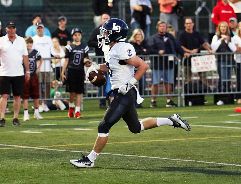 DAN BROOD - Lake Oswego sophomore Casey Filkins runs untouched into the end zone for the Lakers' first touchdown.