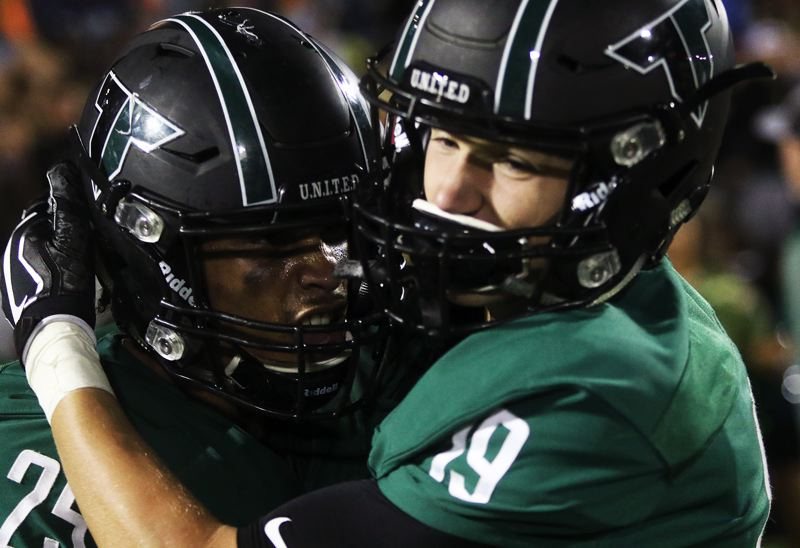 DAN BROOD - Tigard seniors Braden Lenzy (left) and Spencer Smith celebrate following the 31-28 win over Lake Oswego.