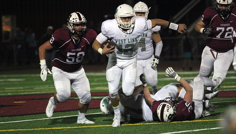 TIDINGS PHOTO: MILES VANCE - West Linn quarterback Ethan Long breaks through the line during his team's 42-21 win over Sherood at Sherqwood High School on Friday.
