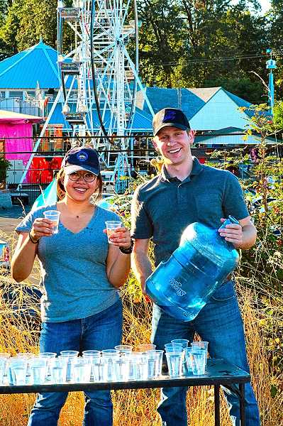 DAVID F. ASHTON - Across from Oaks Amusement Park along the Springwater Trail, Woodstock resident Amy Win and her new friend Spencer Malone handed out water to passing runners.