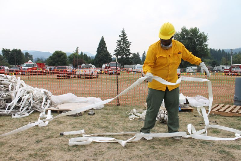 TRIBUNE PHOTO: LYNDSEY HEWITT - Fire fighters at the fire camp headquarters at Hood River County Fairgrounds were 'rolling hoses' that had just come off the line on Saturday.