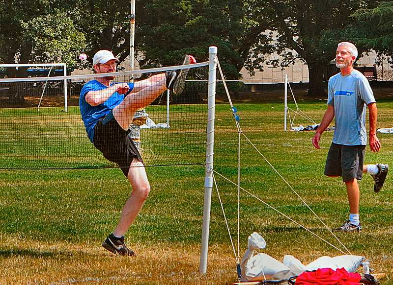 DAVID F. ASHTON - In tournament action at Westmoreland Park, and using only his feet, the player in blue spikes the footbag over the net (you see it airborne, just to the left of his head).