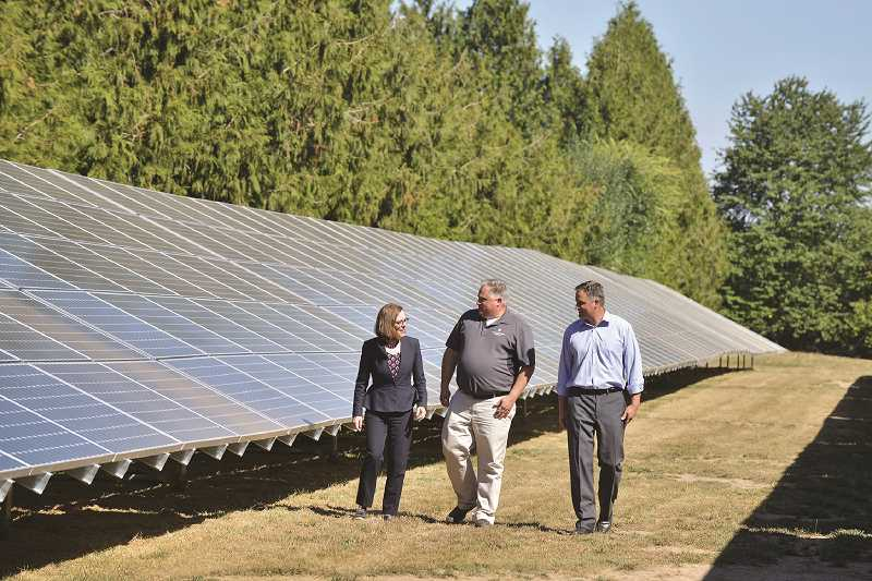 SUBMITTED PHOTO - Larry and Shaun George (right and middle), owners of Northwest Hazelnut, tour the thousand-panel solar array with Governor Kate Brown (left) at the NW Hazelnut processing plant Sept. 1.
