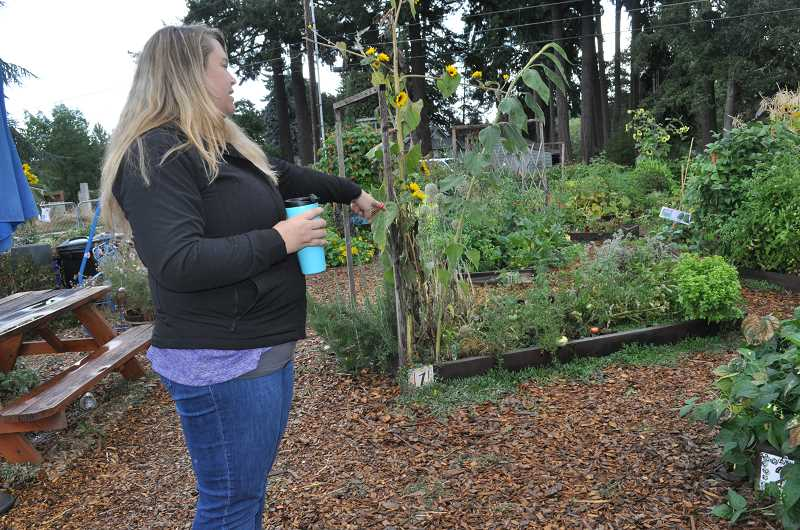 TIMES PHOTO: BLAIR STENVICK - Katrin Dougherty points toward the crops at the Supa Fresh Youth Farm's main site in Tigard.