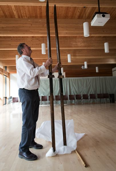 TIMES PHOTO: JAIME VALDEZ - Nordic Northwest executive director Greg Smith stands with long skis dating back to at least the early 20th century, part of an exhibit that just opened at Nordia House on Oregon's Nordic ski history.