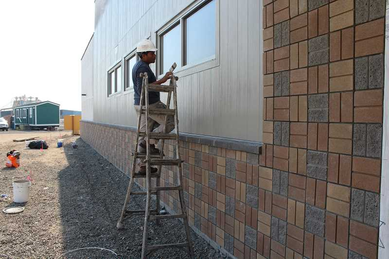 HOLLY M. GILL - Hector Vasquez, of Deschutes Painting, applies a coat of paint to the fiber cement siding on the exterior of the new truck stop, convenience store, fuel station, restaurant and game room, all of which are expected to be completed for opening in March 2018.
