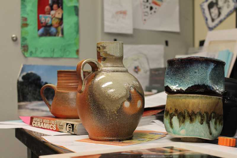 REVIEW PHOTO: CLAIRE HOLLEY - Various ceramics pieces made in the East Creek wood-fire kiln sit on teacher Michael Helle's desk at Lakeridge High School.
