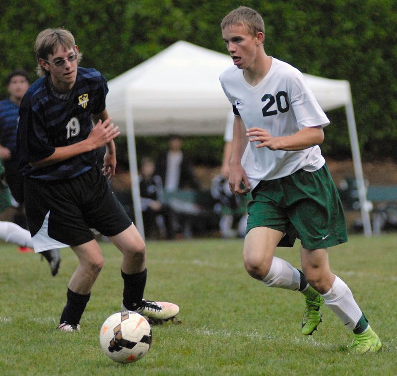 ESTACADA NEWS: MATT RAWLINGS - Estacada's Caleb Brotnov dribbles the ball past a Crook County defender.