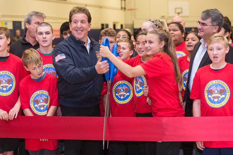 NEWS-TIMES PHOTO: CHRISTOPHER OERTELL - Celebrity fitness instructor Jake Steinfeld cut the ribbon at Neil Armstrong Middle School Thursday morning to welcome students into their new fitness center.